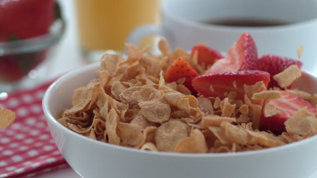 Strawberries falling into cereal in slow motion video