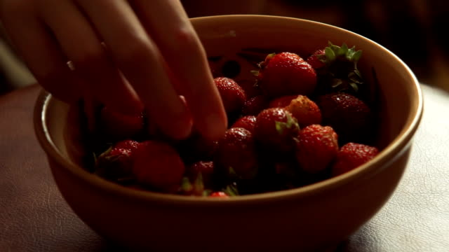 strawberries. Girl hands takes a strawberry from a plate video