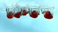 Strawberries splashing into water, Slow Motion video