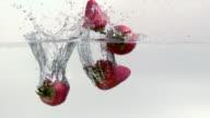 Strawberries splashing into water video
