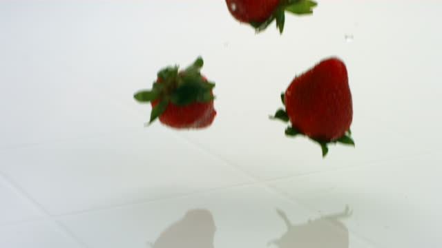 Strawberries splashing, slow motion video
