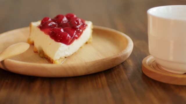 Strawberry and cherry cake on wooden table , Dolly shot right to left video