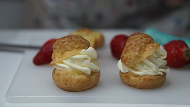 Strawberry cream puffs, choux cream, hand filling cream inside baked pastry video