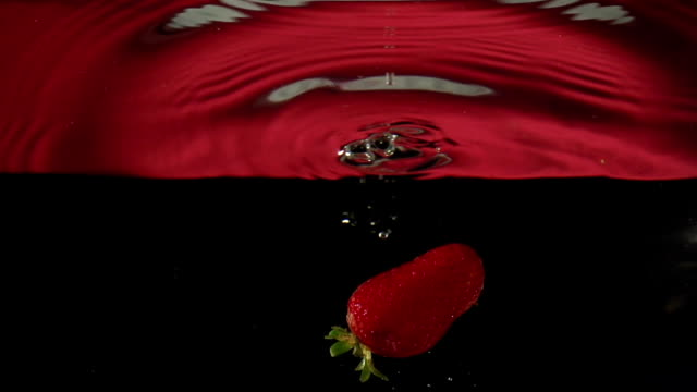 strawberry  drop into water in slowmotion video