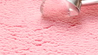 strawberry ice cream scooped out of container spoon is a ball video