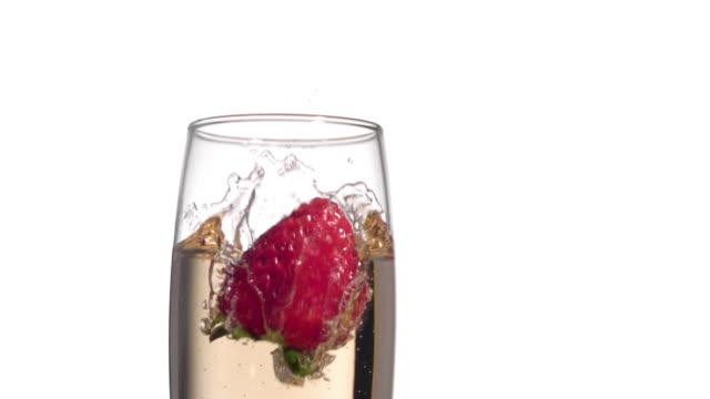 Strawberry splashing into champagne, closeup video