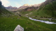 Stream flowing through blooming alpine meadow and lush green woodland set amid high altitude mountain range at sunsets. Valle d'Aosta, Italian Alps. video