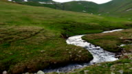 Stream in at green hill in High Snowy Mountains with Clouds. Kavkaz region video