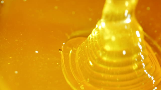A stream of honey flows into a plate, close-up. Slow Motion Picture video