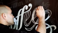 Street artist is doing a chalk graffiti on a black wall in a cafe video