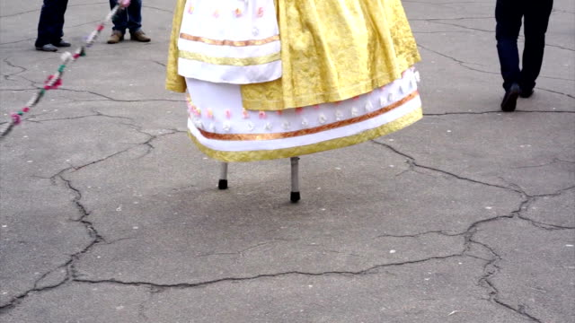 Street entertainer in funny clothes walking on stilts, people in amusement park video