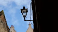 Street lamp in an alleyway with rooftops and chimneys video