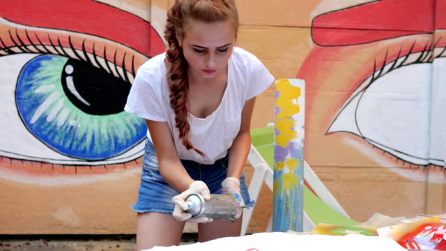 street painting, girl with spray paint in hand, adolescent with aerosol paint at background of graffiti in slow motion video