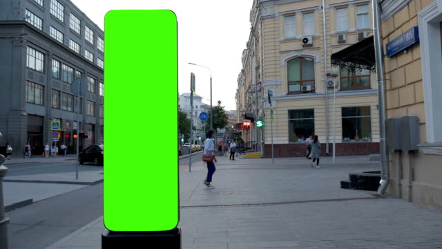 Street pointer with a green screen, located at the crossroads. Background for advertising. Slow movement video