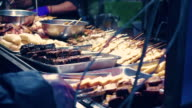 A street vendor cooks skewers of meat on a barbecue video