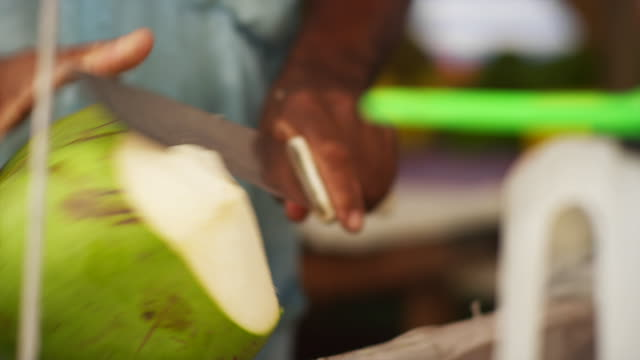 Street vendor cutting a Coconut and pouring fresh Coconut water video