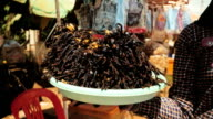 Vendor holding a stack of fried tarantulas on a bowl video