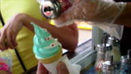 Street vendor sprinkles ice cream waffle cone by sugar red hearts video