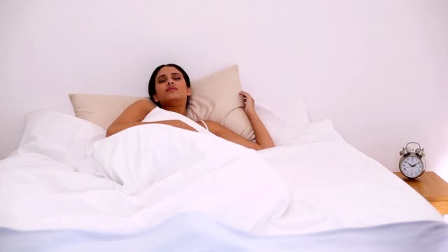 Stressed beautiful woman waking up too late video