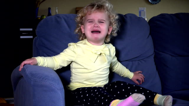 Stressed cute little girl crying sitting on sofa video