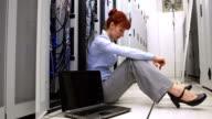 Stressed technician sitting on floor beside open server video