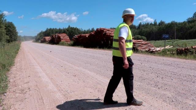 Stressful lumberjack walking near logs of pile video