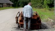 Stressful man on burned down car wreck on the side of the road video
