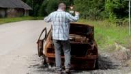 Stressful man talking on smart phone and kick car wreck video