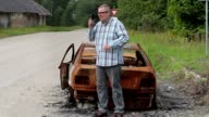 Stressful man using smart phone near burned down car wreck on the side of the road video