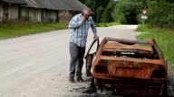 Stressful man walking near the car wreck and talking on smart phone video