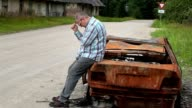 Stressful man worry near burned down car wreck on the side of the road video