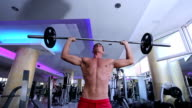 Strong, active and intense man lifting weights in gym video