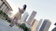 Strong angle on Asian woman in gold dress in front of LA skyline video