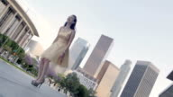 Strong angle on Asian woman in gold dress jumping front of LA skyline video