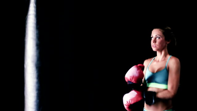 Strong Female Fighter Exercising for Self Defense with Boxing Gloves and Body Bag. video