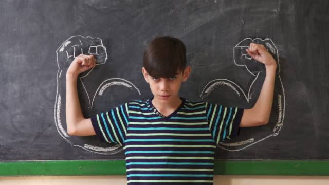 Strong Male Child Showing Muscles In Classroom At Lesson video