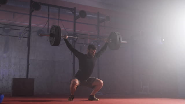Strong man doing barbell snatch exercise at the gym in slow motion video