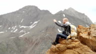 Strong man hiker taking photo with smart phone at mountain peak. Marvelous daybreak. video