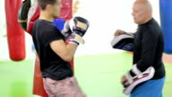 Strong man kickboxer practicing with trainer video