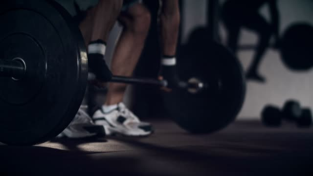 Strong man lifting weights in gym video