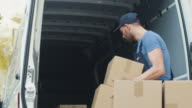 Strong Mover Loads His Van with Cardboard Boxes from the Street. video