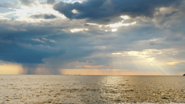 Strong rain far into the sea and the setting sun with beautiful rays. Amazing sunset over the sea video