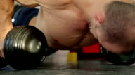 Strong sportive man doing dumbbell push-up exercise, preparing for competition video