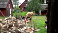 Strong villager boy prepare natural wood fuel and rural houses. FullHD video