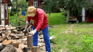Strong villager guy prepare natural wood fuel and rural houses. video
