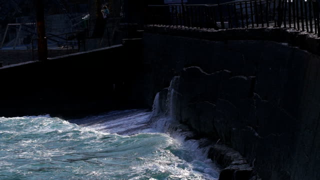 Strong waves breaking on the stone slabs waterfront video