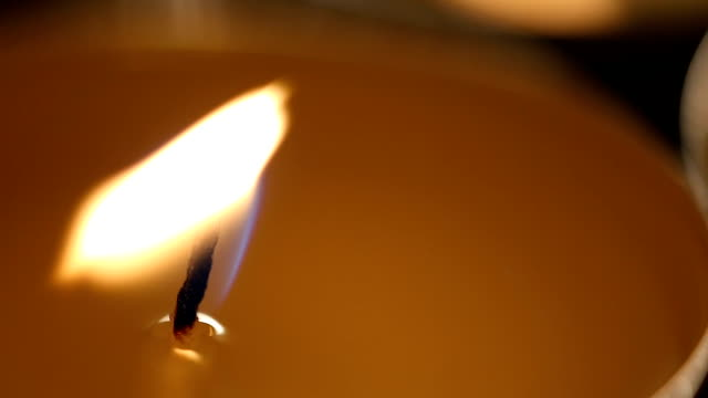 Strong wind blowing at weak candle flame, attempt to resist terminal illness video