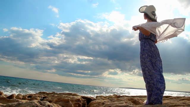 Strong woman standing on sea rocks, enjoying freedom, feeling of video