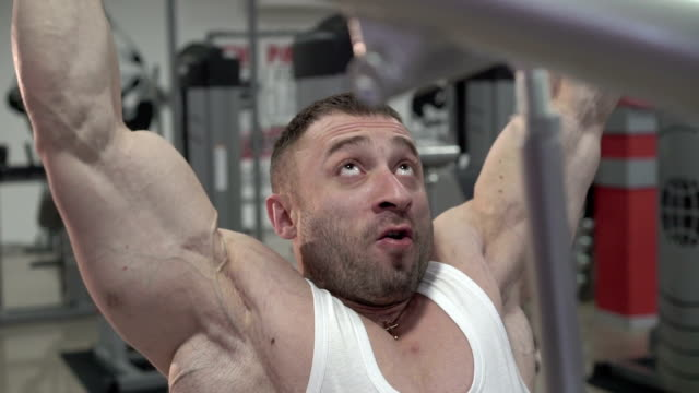Strong world champion doing exercises for arms, big biceps. Slow motion video