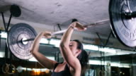 Strong young woman lifting heavy weights at gym, slow motion video